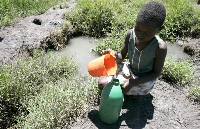 A girl collects drinking water from a stream in Glen Norah, Harare November 27 2008. Zimbabwe, which is battling a serious cholera outbreak amid a worsening economic crisis, is set to get vaccines from China to fight the disease, state media reported on Thursday. REUTERS/Philimon Bulawayo (ZIMBABWE)