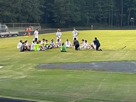 The Gators get tactics from Coach Solakoglu, as they wait to take on the second half.